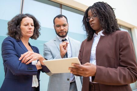 Focused business people with tablet computer. Low angle view of serious multiethnic male and female coworkers standing and using digital tablet together. Technology concept