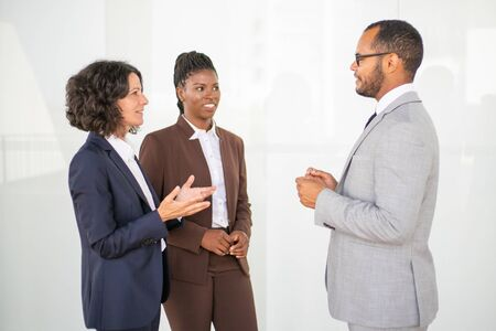 Multiethnic business partners discussing project. Business man and women standing near white office wall, talking, gesturing, smiling. Partners meeting concept