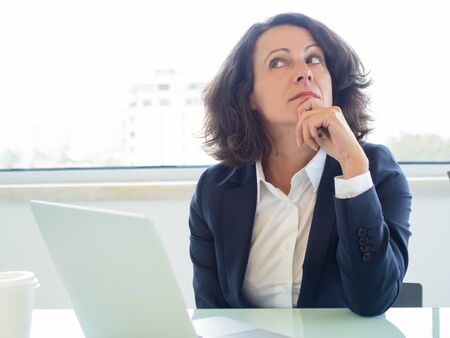Pensive CEO thinking over business strategy. Businesswoman sitting at workplace with open laptop, leaning chin on hand and looking up. Business woman at workplace concept