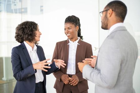 Multiethnic business team discussing project. Business man and women standing in office corridor, talking, gesturing, chatting, laughing. Corporate meeting concept