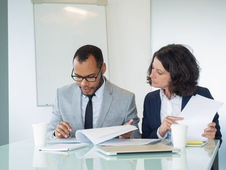 Serious professionals studying reports or agreement text. Serious focused business man and woman sitting at meeting table and reading documents together. Expertise concept Zdjęcie Seryjne