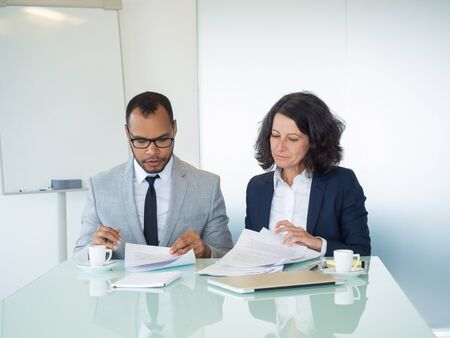 Business professionals examining contract text. Business man and woman sitting at meeting table and reading papers together. Paperwork and teamwork concept