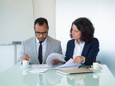 Business colleagues checking agreement text. Business man and woman sitting at meeting table and reading documents together. Teamwork concept