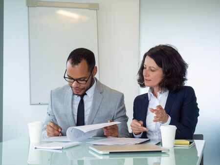 Serious focused lawyers reviewing documents. Business man and woman sitting at meeting table and reading papers together. Paperwork concept