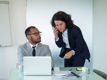 Senior employee calling on phone and helping new colleague with corporate software. Business man sitting at laptop and looking at female coworker. Mentorship concept
