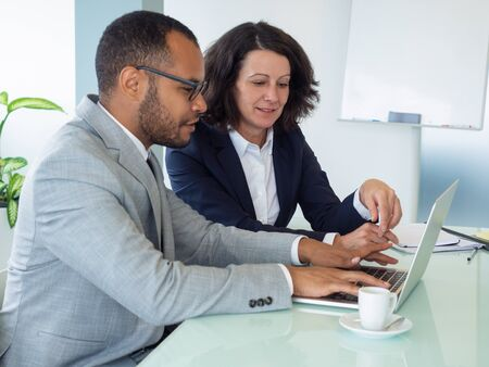 Female mentor teaching male newcomer at laptop. Business man and woman using computer in boardroom together. Mentorship concept