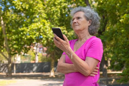 Serious focused old lady listening to voice message on phone in park. Senior grey haired woman in casual standing on walkway and using smartphone. Wireless connection concept