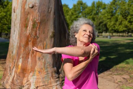 Happy old lady warming up for morning exercise in park. Senior grey haired woman in casual sitting on bench and stretching hand. Age and fitness concept Standard-Bild - 129175056