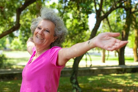 Positive carefree old lady enjoying morning exercise outdoors. Senior grey haired woman in casual standing in park, spreading hands and smiling. Active senior woman concept Standard-Bild - 129175057