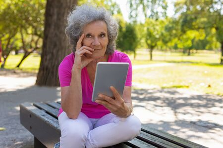 Pensive old lady with tablet enjoying leisure in park. Senior grey haired woman in casual sitting on park bench, thinking and holding tablet. Tablet using concept Standard-Bild - 129175070