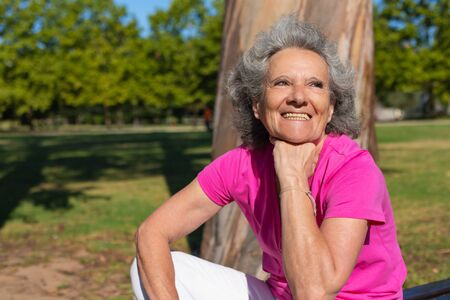 Cheerful excited old lady spending great time in park. Senior grey haired woman in casual sitting on bench outdoors, looking away and smiling. Resting in park concept Standard-Bild - 129175073