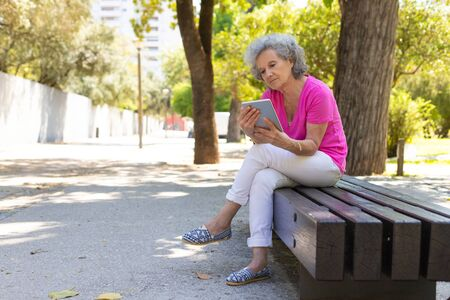 Pensive peaceful old lady reading on tablet screen in park. Senior grey haired woman in casual sitting on park bench and using tablet. Wi-Fi outdoors concept Standard-Bild - 129175075