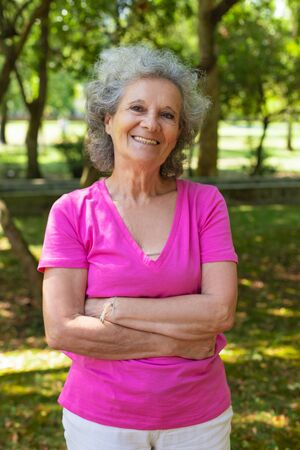 Happy joyful old lady posing outdoors. Senior grey haired woman in casual standing in park with arms folded, looking at camera and smiling. Outdoor female portrait concept Standard-Bild - 129175077