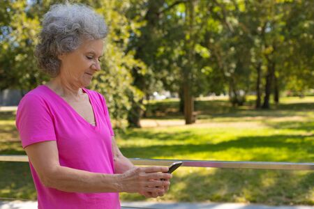 Positive focused old lady texting message while walking on parkway. Happy senior grey haired woman in casual using mobile phone in park. Wireless connection concept Standard-Bild - 129175078
