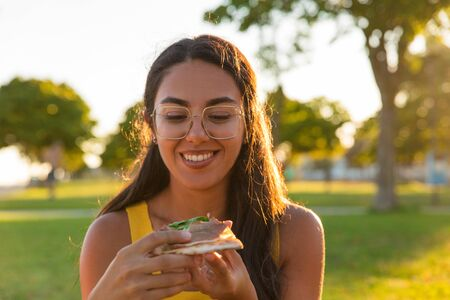 Happy Latin woman enjoying dinner in park. Beautiful young woman sitting on grass and eating pizza slice. Takeaway dinner concept 版權商用圖片 - 129175079