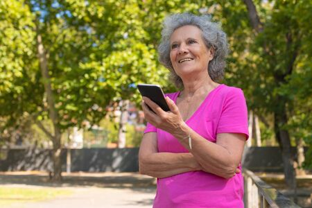 Happy old lady listening to voice message on cellphone in park. Senior grey haired woman in casual standing on walkway, using mobile phone and smiling. Voice message concept Standard-Bild - 129175082