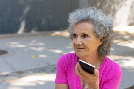 Thoughtful excited old lady listening to voice message on phone. Senior grey haired woman in casual sitting on park bench, using smartphone and looking away. Communication outdoors concept Standard-Bild - 129175102