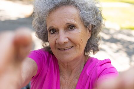 Delighted old lady taking self picture in park. Senior grey haired woman in casual holding gadget and smiling at phone camera. Selfie concept Standard-Bild - 129175110