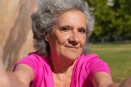 Cheerful old lady posing for selfie in park. Self portrait of senior grey haired woman in casual with grass and trees in background. Age and digital technology concept Standard-Bild - 129175111