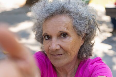 Positive old lady taking selfie in park. Senior grey haired woman in casual holding gadget with hand and looking at phone camera. Self shot concept Standard-Bild - 129175117