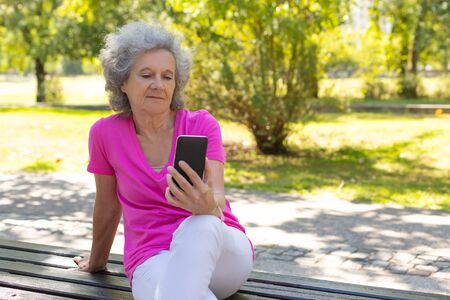 Pensive calm old lady relaxing in park and reading on phone screen. Happy senior grey haired woman in casual sitting on bench and using smartphone. Reading on phone screen concept Standard-Bild - 129175124