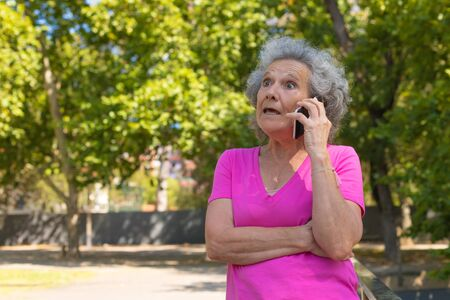 Excited surprised old lady getting shocking news from phone call. Senior grey haired woman with wide eyes standing outdoors and talking on mobile phone. Shock concept Standard-Bild - 129175087