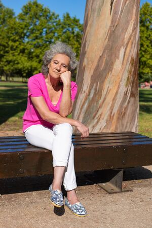Tired old lady relaxing in park. Senior grey haired woman in casual sitting on bench, leaning head on hands and looking into vacancy. Resting in park concept Standard-Bild - 129175091