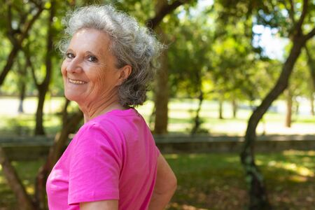 Excited happy old lady walking in park. Side and back of senior grey haired woman in casual turning smiling face to camera. Senior woman portrait concept Standard-Bild - 129175098