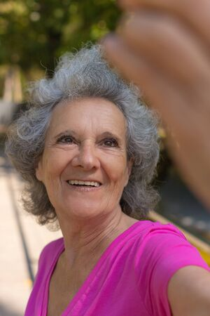 Excited happy old lady taking selfie outdoors. Senior grey haired woman in casual talking through video call while walking in park. Video connection concept Standard-Bild - 129175108