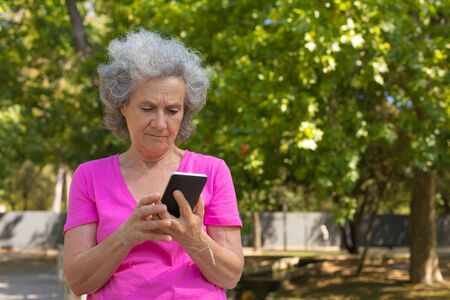 Pensive confused old lady reading message on cell screed in park. Senior grey haired woman in casual standing on walkway, using mobile phone and smiling. SMS concept