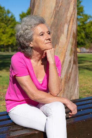 Pensive tired old lady waiting someone in park. Senior grey haired woman in casual sitting on bench, leaning head on hand and looking away. Waiting in park concept