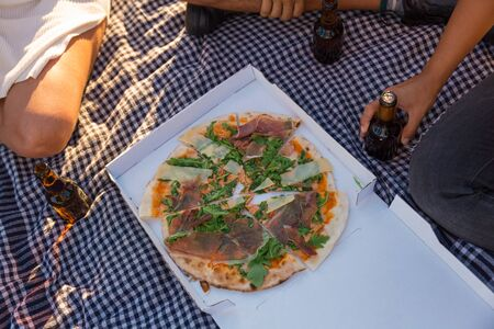 Sliced pizza in box and bottles of beer on picnic blanket. Man and women sitting on plaid around box of pizza and drinking beer. Pizza outdoors concept 版權商用圖片 - 129174578