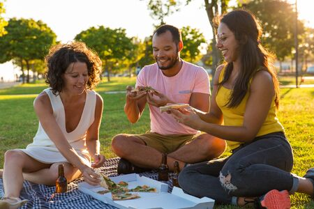 Group of happy closed friends eating pizza in park. Man and women sitting on plaid around pizza and bottles of beer, taking slices from box and talking. Dinner outdoors concept