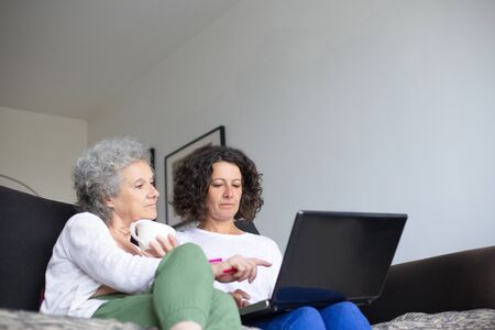 Senior mother with adult daughter using laptop. Low angle view of elderly woman sitting on couch with middle aged daughter and using laptop computer together. Technology concept