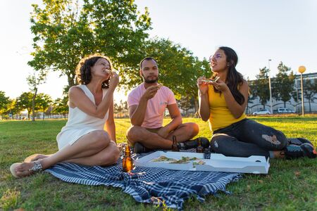 Group of happy closed friends having dinner outdoors. Man and women sitting on plaid around pizza and bottles of beer, taking slices from box and eating. Picnic at sunset concept