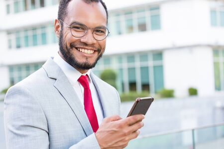 Happy joyful businessman with smartphones posing outdoors. Young Latin business man holding mobile phone and smiling at camera. Digital technology concept