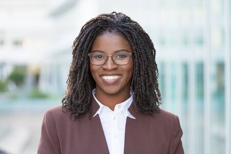 Happy successful business professional posing outside. Attractive young black business woman wearing eyeglasses and smiling at camera. Female business portrait concept Stock fotó