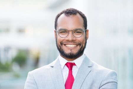 Happy successful businessman posing outside. Handsome young Latin business man wearing eyeglasses and red tie and smiling at camera. Business portrait concept