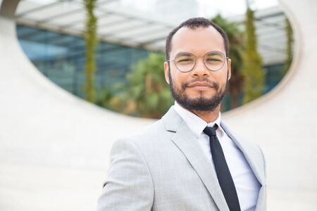 Positive confident businessman posing outside. Handsome business man in eyeglasses and office suit and tie standing for camera and smiling. Proud business leader concept 写真素材