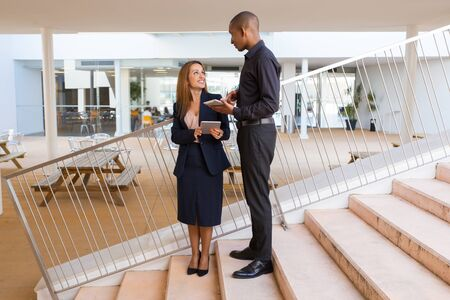 Two business colleagues discussing ideas for project in office hallway. Business man and woman standing on stairs, holding digital tablets and talking. Coworkers concept Stockfoto