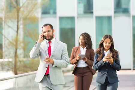 Serious Latin businessman speaking on mobile phone while walking down city street. Man in office suit talking on cellphone outside, women using gadgets behind him. Phone talk concept