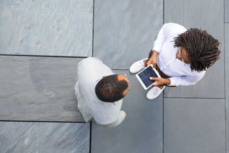 Two colleagues meeting near office and discussing project. Top view of business man and woman standing outside, talking and using tablet. Collaboration concept Stockfoto