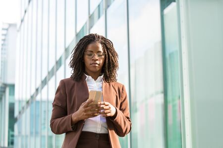 Confident businesswoman texting message outside. Black woman in office suit standing near urban glass wall and using mobile phone. African American business woman concept