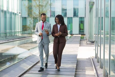 Happy businessman showing content on tablet to female colleague. Business man and woman walking outside, using tablet, talking, smiling, laughing. Communication concept