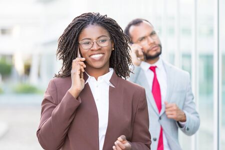 Happy young businesswoman talking on cell outside. Black business woman walking down city street and calling on phone, man speaking on cellphone behind her. Mobile communication concept