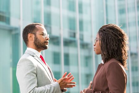 Serious multiethnic business colleagues discussing project outside. Business man and woman talking outside office, urban building in background. Business conversation concept Stockfoto