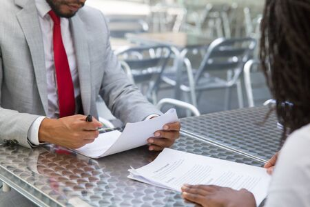 Businesspeople meeting in street cafe for signing contract. Business man and woman reading document, writing in paper, holding pen. Partnership or paperwork concept Stockfoto