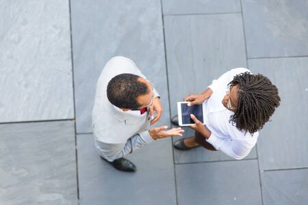 Two professionals meeting near office and discussing work issues. Top view of business man and woman standing outside, talking and holding tablet with blank screen. Businesspeople concept Stockfoto