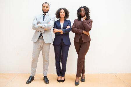 Confident business people posing with arms folded. Business man and women standing over white background and looking at camera. Team portrait concept