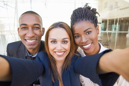 Happy businesswoman taking group selfie with team. Self portrait of successful multiethnic business man and women. Corporate selfie concept